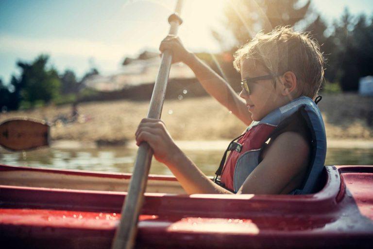 junge in boot mit paddel